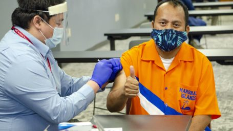 Marshallese man receiving vaccine and giving thumbs up